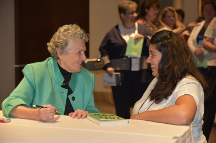 Sister Joan signs a book for participant Gina Ciliberto.